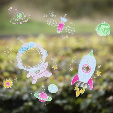 Window decorations with outer space designs using chalk markers