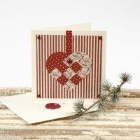 Een kerstkaart met gevlochten hart en een waszegel op de envelop