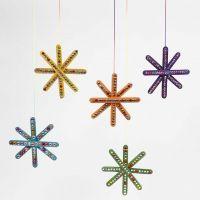 Een ster van gekleurde ijsstokjes, gedecoreerd met strasstenen