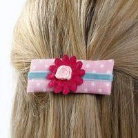 Haarspeld gemaakt van karton, gedecoreerd met textiel, lint en bloemen