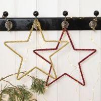 Metalen kerstster gedecoreerd door haken