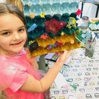 De zee en de vis uit versierde ei-dienbladen en plastic afval